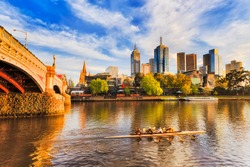 Golden sunlight and morning hour over Melbourne city CBD landmark high-rise towers on waterfront of Yarra river and Princes bridge with blurred exercising rowing team.