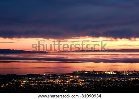 Golden sunlight peeks through dark storm clouds over the Pacific ocean and the city lights of Santa Barbara, California.
