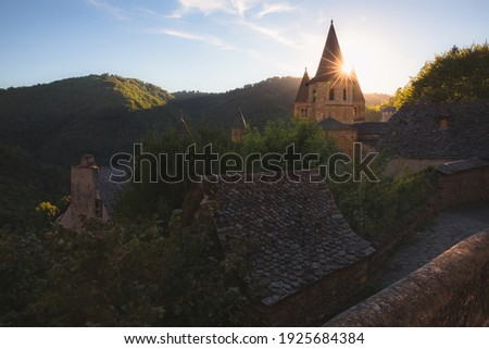 Golden sunrise or sunset light over the quaint and charming medieval French village of Conques, Aveyron, and Abbey Church of Sainte-Foy, in Occitanie France. Photo stock ©