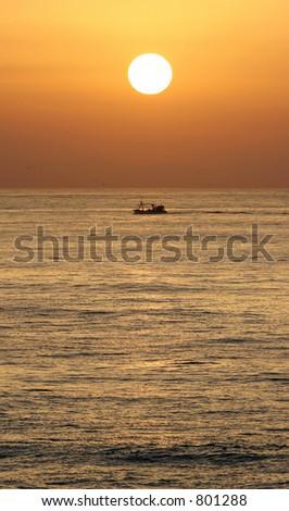 Golden sunrise over mediterranean sea near Marbella on the Costa del Sol as boat sails past