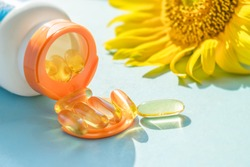 Golden Sunscreen pills with bottle and sunflower on blue background in sunlight. Dietary supplements, protect skin from the sun. Take pill and avoid the burn