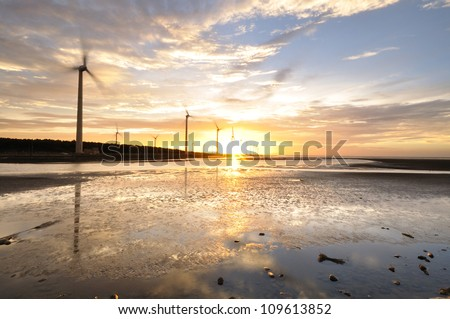 golden sunset at a wind-power station - stock photo