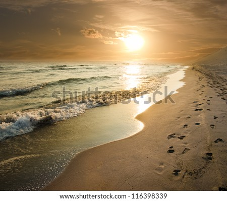 Albania golden sunset on the sea shore and footprints in the sand