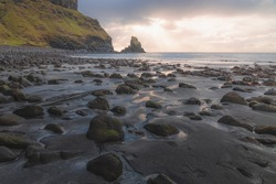 Golden sunset or sunrise light on seascape and sea stack along the rocky shore at low tide at Talisker Bay Beach on the Isle of Skye, Scotland