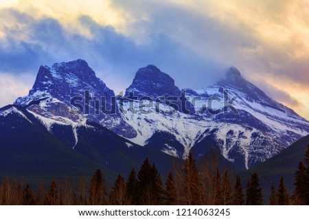 Golden sunset over the famous Three Sisters mountain peaks of Faith, Charity and Hope in the Canadian Rockies of Canmore with moving clouds and heavy fog. #1214063245