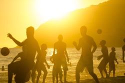 Golden sunset silhouettes of Brazilians playing keepy uppy altinho beach football soccer at Posto Nove, on Ipanema Beach, Rio de Janeiro, Brazil