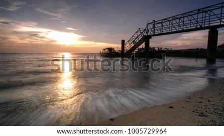 Golden Sunset with amazing waves at Puteri Beach Old Jetty Old Jetty, Malacca, Malaysia.  #1005729964