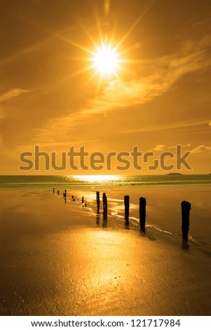 golden sunshine over the beach breakers in Youghal county Cork Ireland on a summers day