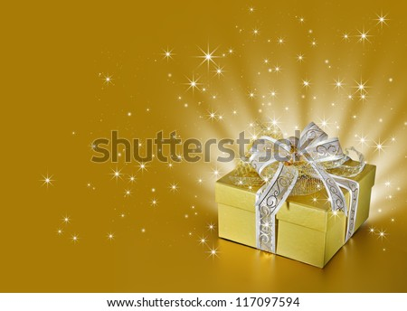 Golden surprise gift box or present with ribbon and bow, light beams and sparkling stars