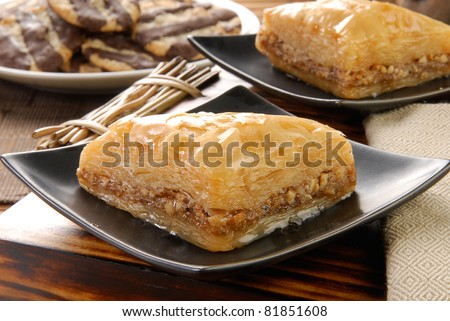 Golden sweet baklava with oatmeal cookies with fudge stripes in the background