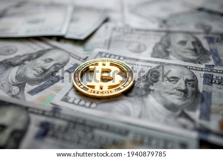 Golden symbolic coin Bitcoin on banknotes of one hundred dollars. Exchange bitcoin cash for a dollars. Cryptocurrency on US dollar bills. Digital modern method of payment. Savings, investments concept