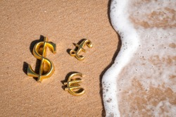 Golden three-dimensional symbols of international dollar, euro and pound currency with wave encroaching on the sand of an empty sunny beach