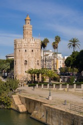 Golden Tower in Seville (Torre del Oro, Sevilla) Andalusia, Spain, with the Guadalquivir river and blue sky background