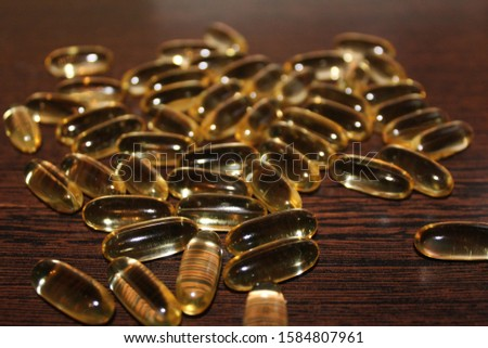 Golden transparent capsules on a brown background