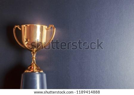 Golden trophy on black background