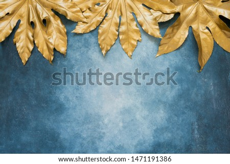 Golden tropical leaves on blue backdrop. Minimal summer exotic concept with copy space. Copy space, top view.