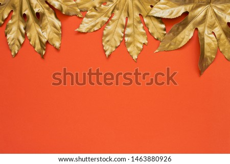 Golden tropical leaves on bright coral color backdrop. Minimal summer exotic concept with copy space. Copy space, top view.