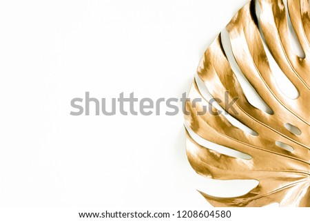 Golden tropical palm leaf Monstera on white background. Flat lay, top view minimal concept.