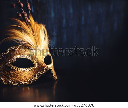 Golden venetian ball mask over dark background with copyspace. Masquerade party or holiday event celebration concept. Stock photo ©
