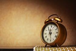Golden vintage alarm clock showing five to twelve