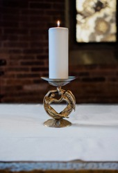 golden vintage candle holder with large white pillar candle burning in an ancient church, candle burning on table in an ancient church