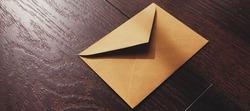 Golden vintage envelope on wooden background, newsletter and message concept