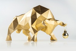 Golden volumetric paper bull with a Christmas ball on the horn on a white glossy background, symbol of the year