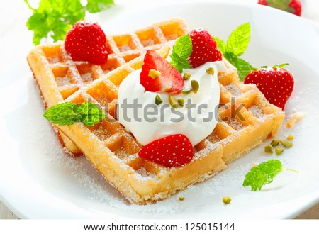 Golden waffle topped with fresh sliced strawberries and cream and sprinkled with sugar for a delicious dessert