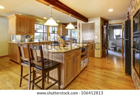 Golden warm wood kitchen with large island and back appliances.