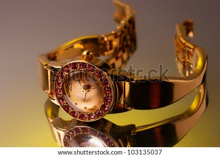 Golden watch decorated with gems with reflection