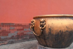 Golden water tank with lion statue against red wall in the Forbidden city
