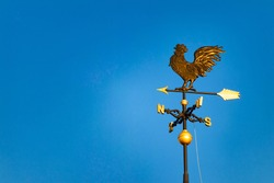 Golden weathercock shining in the blue sky
