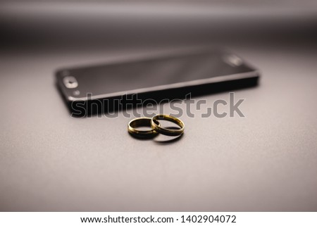 golden wedding rings on a mobile phone. Concept of infidelity or virtual betrayal through the smartphone. Foto d'archivio ©
