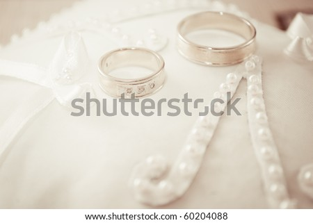 stock photo golden wedding rings on small white cushion