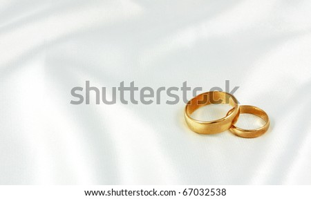 Golden wedding rings on white silk