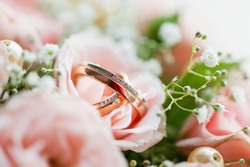 Golden wedding rings with diamonds lie inside rose flower in the bouquet. Symbol of love and marriage.