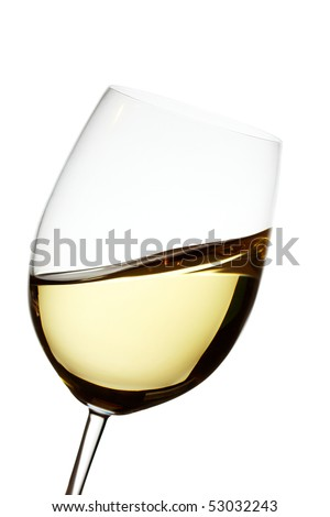 Golden white wine in a crystal glass showing waves
