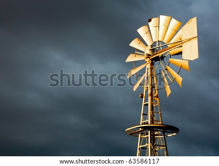 Golden Windmill Illuminated in Light with Stormy Clouds