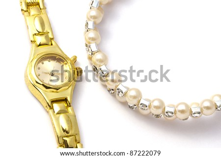 Golden wrist watch and necklace on white background