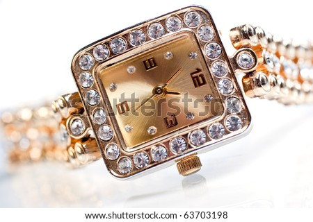Golden wristwatch with gems isolated over white