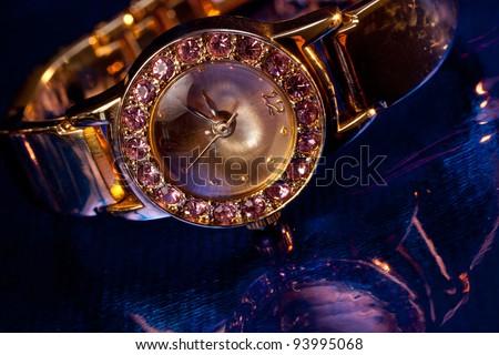 Golden wristwatch with gems on blue background