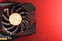 Golden XRP Ripple Coin cryptocurrency on a Black video Card with red backlight, copy space. Bitcoin mining concept
