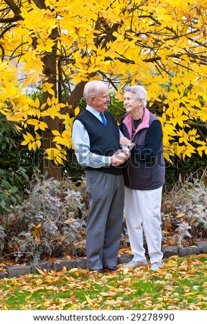 Golden Years Senior couple sharing an affectionate moment near tree with golden leaves