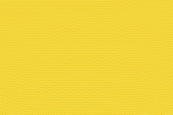 Golden yellow background from a textile material with pattern, closeup. Structure of banana yellow fabric with punching texture. Perforated cloth backdrop.