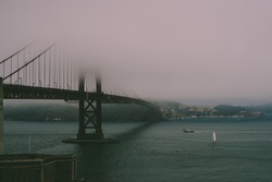 Goldengate bridge covered in mist with boat passing underneath