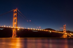 GoldenGate Bridge San Francisco at night with reflections in water