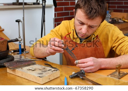 Goldsmith in workshop. Making of jewelery. Handmade. Intentional shallow depth of field.
