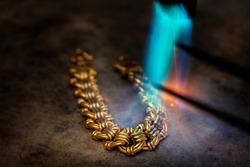 Goldsmith makes gold necklace, use high fire blow soften the gold for easy formatting,which tradition method.