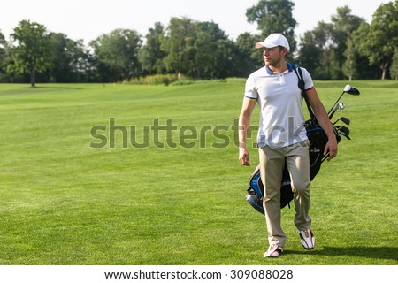 Golf and golfer concepts. Golf player in  trucker hat walking and carrying bag with golf clubs on course during summer time.