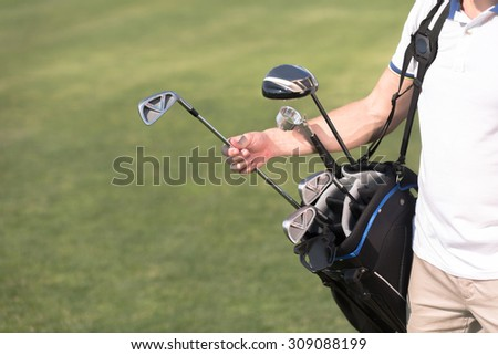 Golf and golfer concepts. Man in white T-shirt removing a driver from golf bag. He is going to spend his time on golf green course.